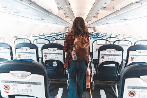 Woman walking down airplane aisle